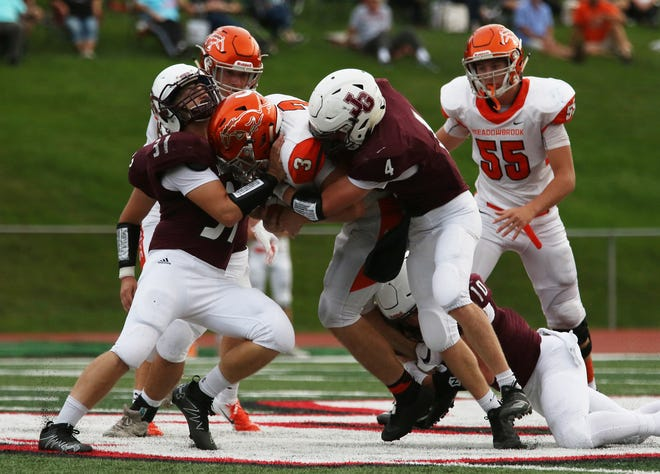 John Glenn's Parker Zachrich (4) and Josh Conner tackles Meadowbrook's Brady Blattner earlier this season. The Muskie defense has been stellar over the final six weeks, allowing a total of 21 points entering Saturday's playoff game at Indian Valley.