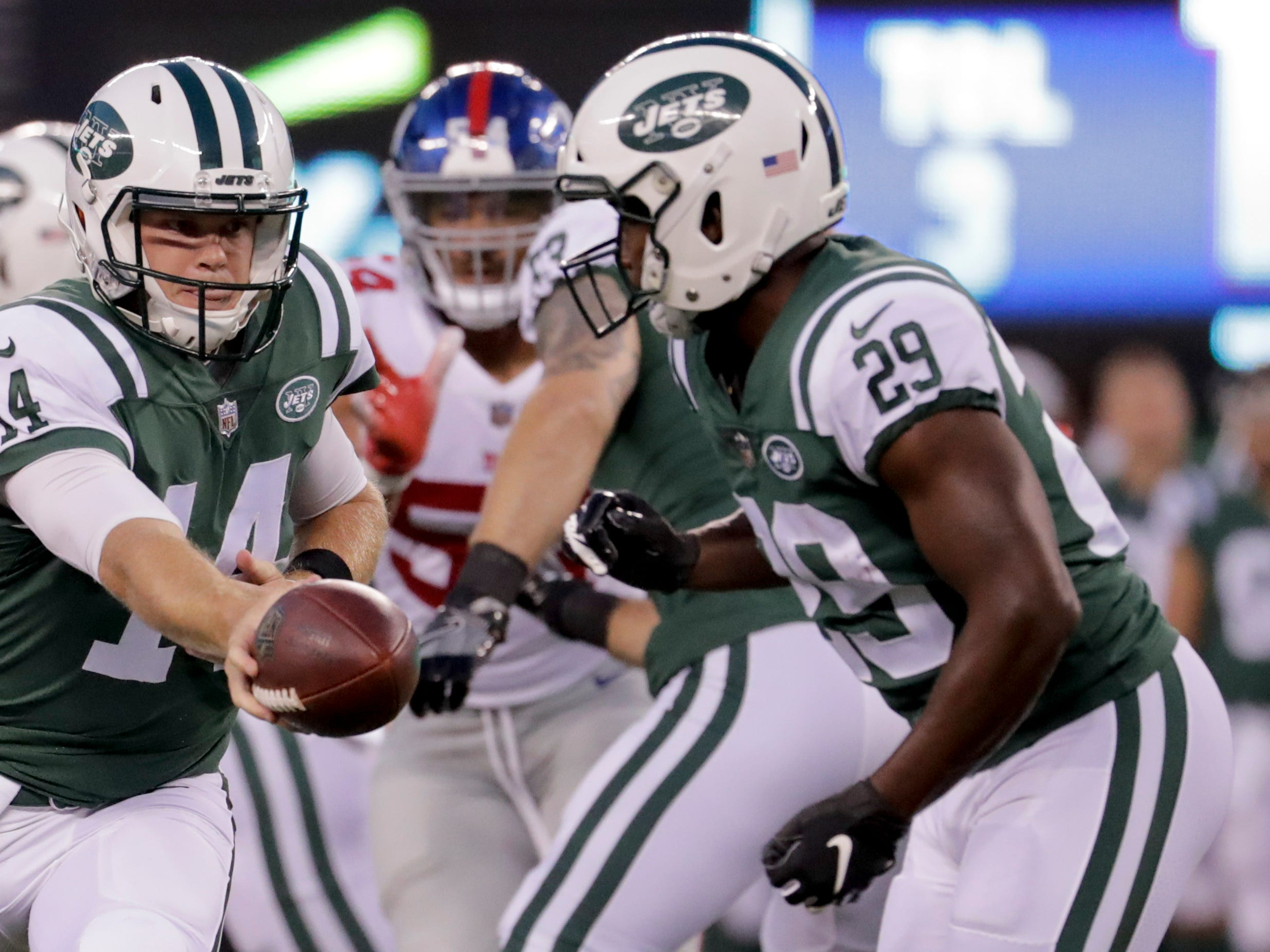 New York Jets quarterback Sam Darnold (14) hands off the ball to running back Bilal Powell (29) during the first quarter of an NFL football game, Friday, Aug. 24, 2018, in East Rutherford, N.J.