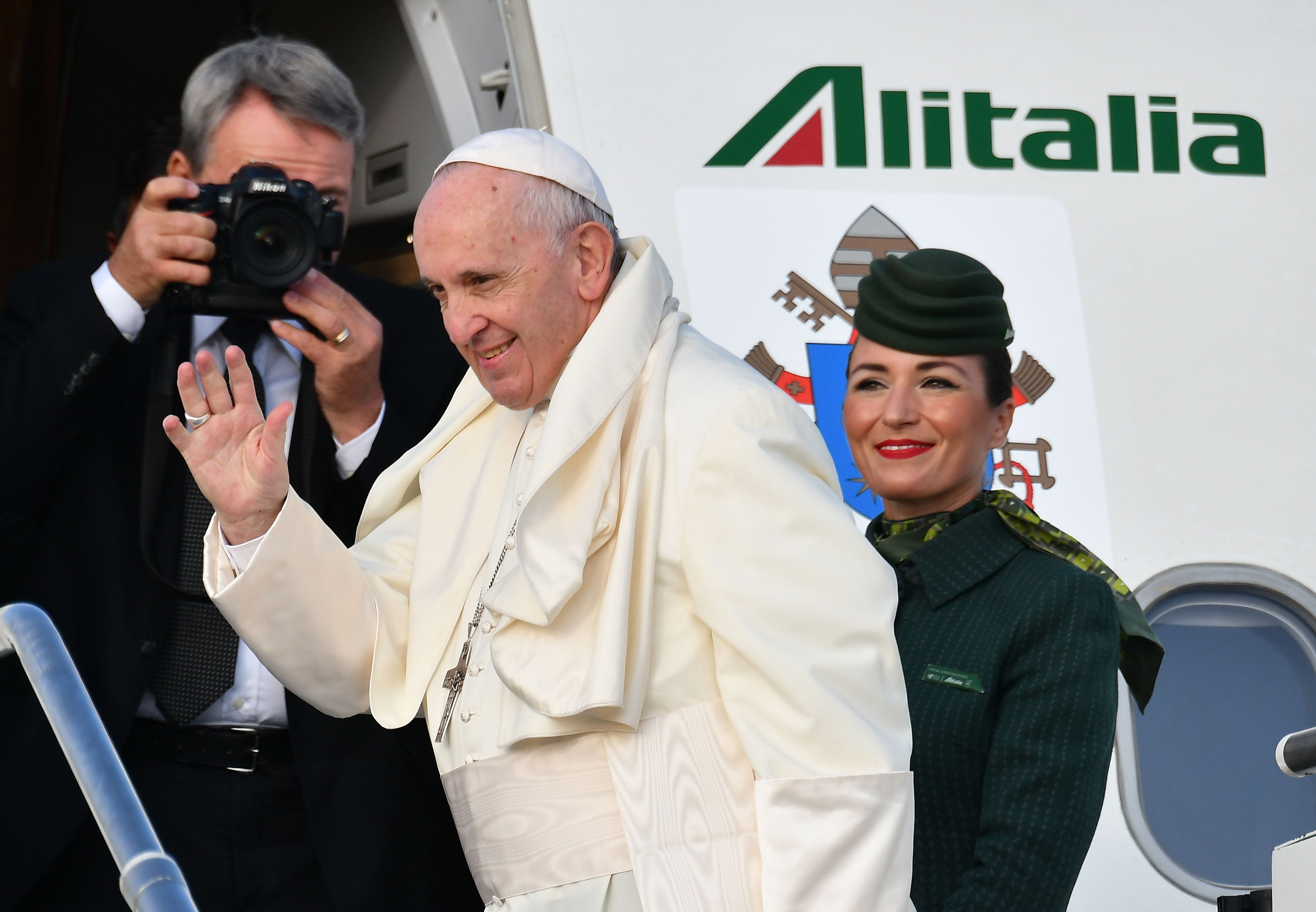 Pope Francis waves as he boards the plane on his way to the his two-day pastoral trip to Ireland.