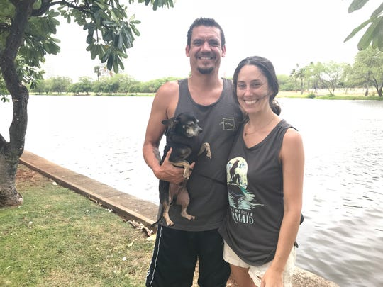 Desiree Beveridge, who with her partner Eric Smythe was out walking their dog Bruce Wayne along the Ala Wai Canal in Honolulu Friday afternoon before the onset of Tropical Storm Lane.