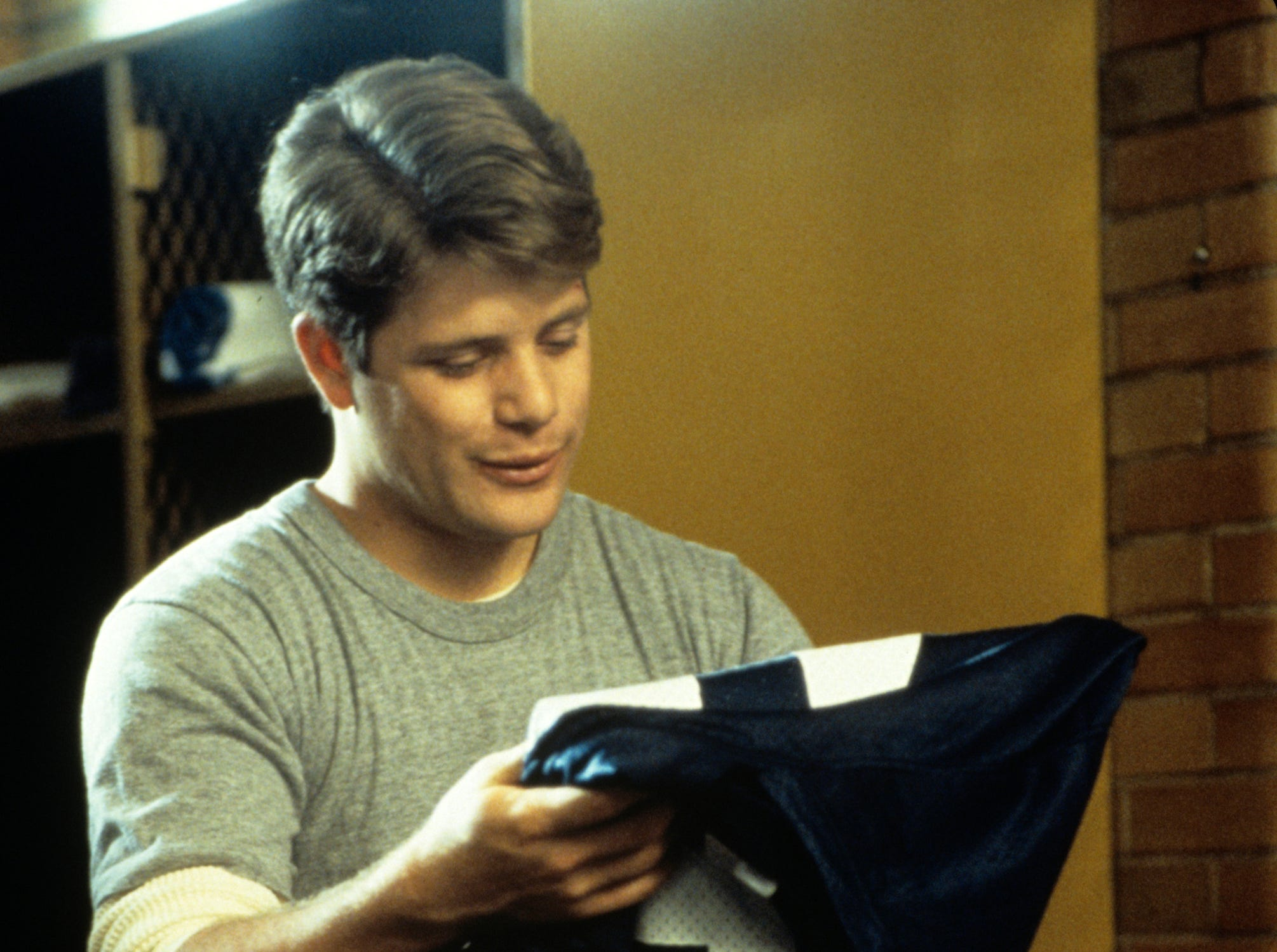 "Rudy Ruettiger (Sean Astin) puts on his game jersey in ""Rudy."""