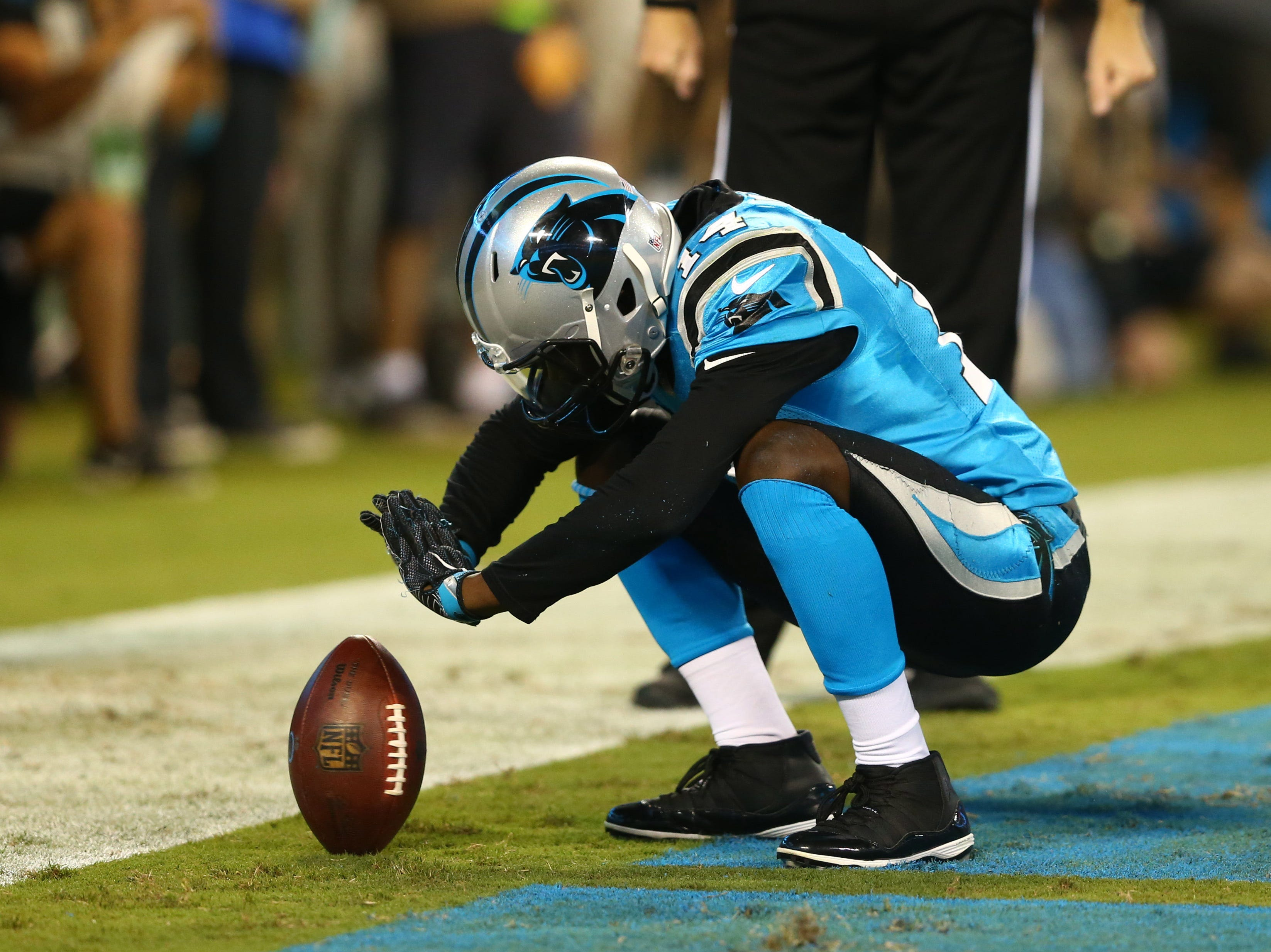 Carolina Panthers wide receiver Mose Frazier (14) spins a football after a touchdown in the fourth quarter against the New England Patriots at Bank of America Stadium.