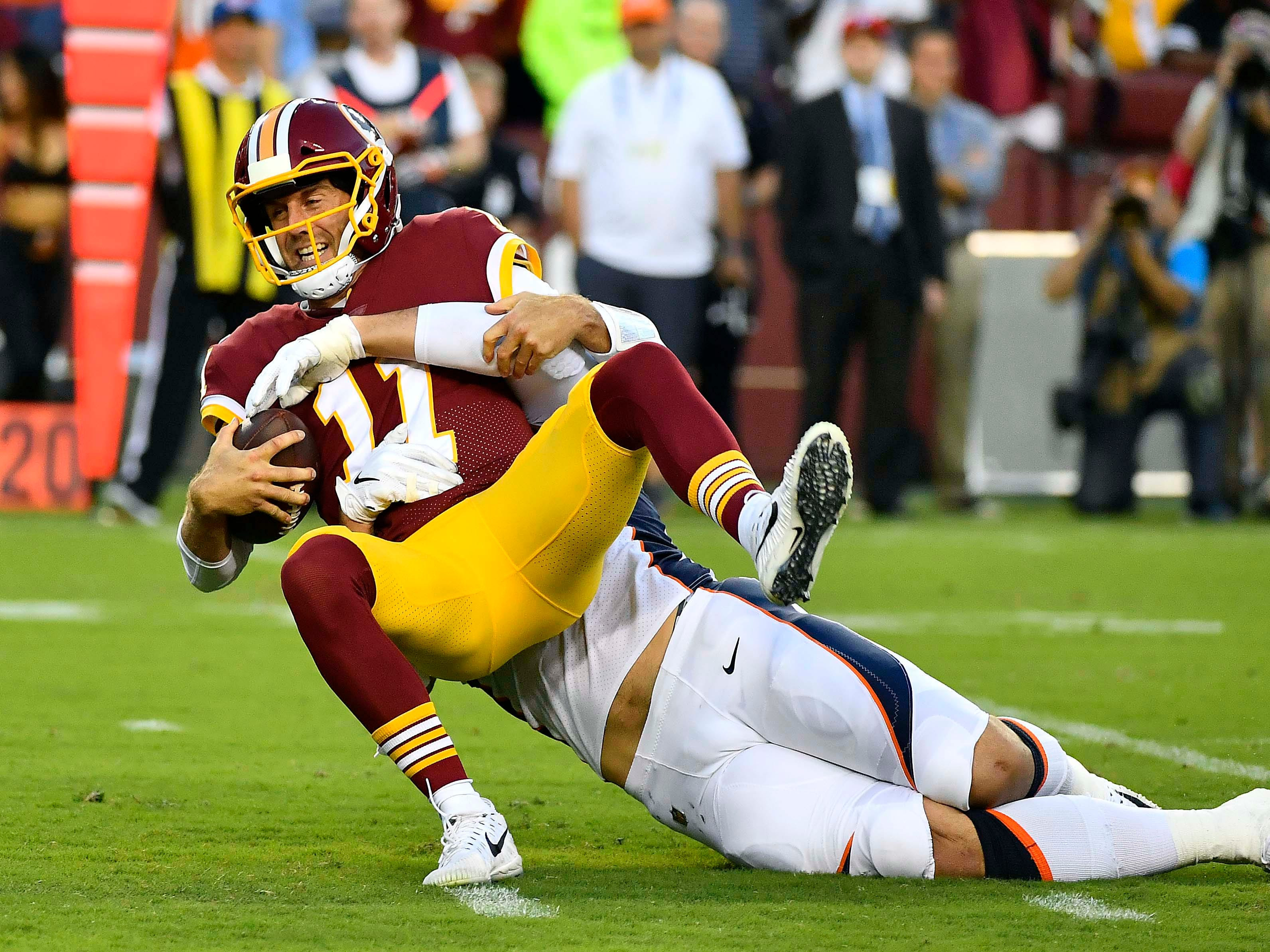 Washington Redskins quarterback Alex Smith (11) is sacked by Denver Broncos defensive end Adam Gotsis (99) during the first half at FedEx Field.