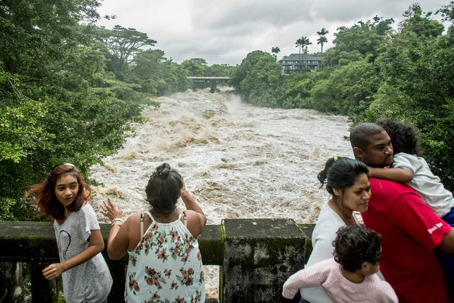 People watch from the Puueo Street bridge as the Wailuku River rages below them in Hilo, Hawaii, on Thursday.  The city of Hilo, population 43,000, was flooded with waist-high water.