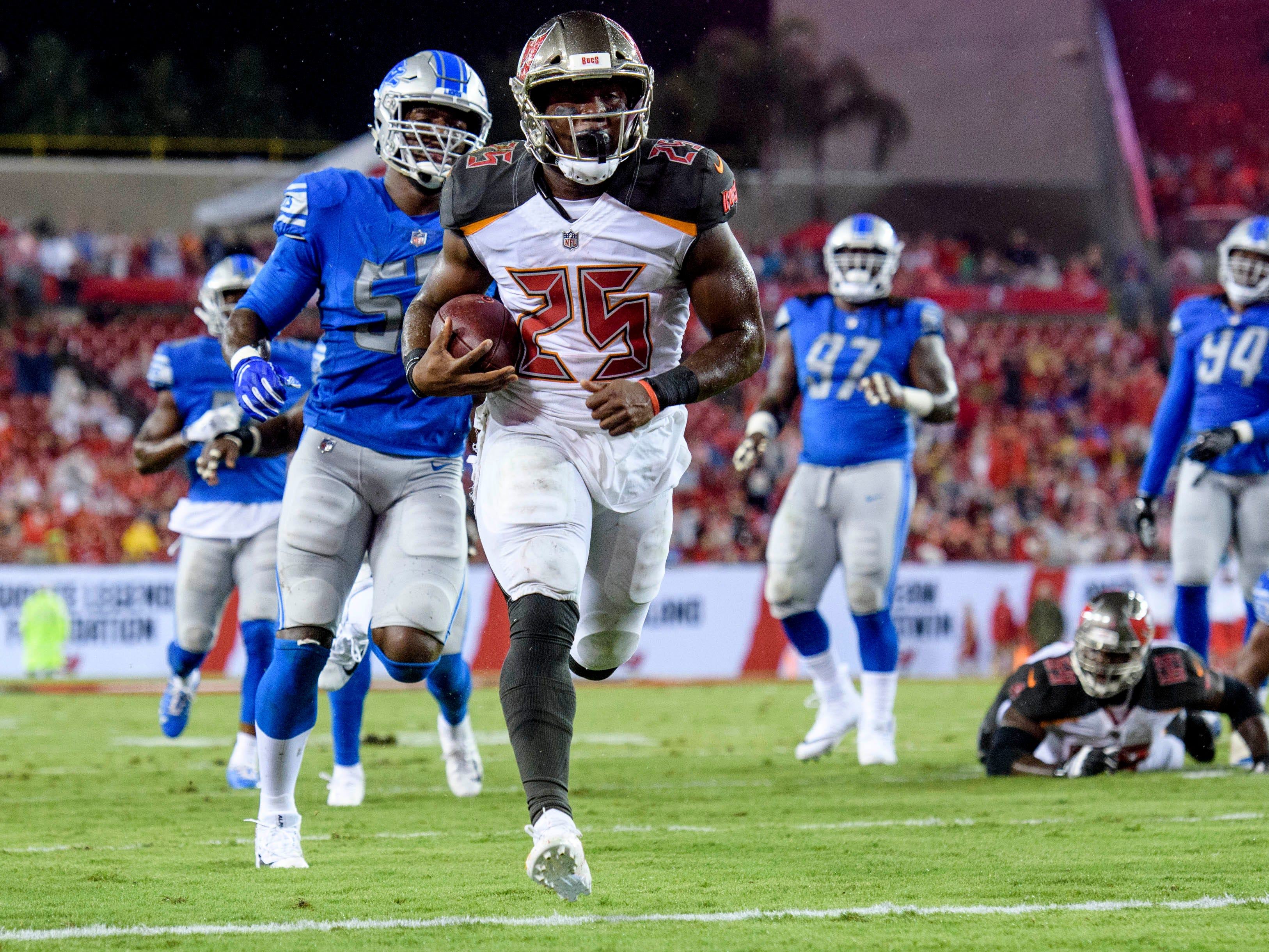 Tampa Bay Buccaneers corner back De'Vante Harris (25) runs the ball in for a touchdown during the first half of the game against the Detroit Lions at Raymond James Stadium.
