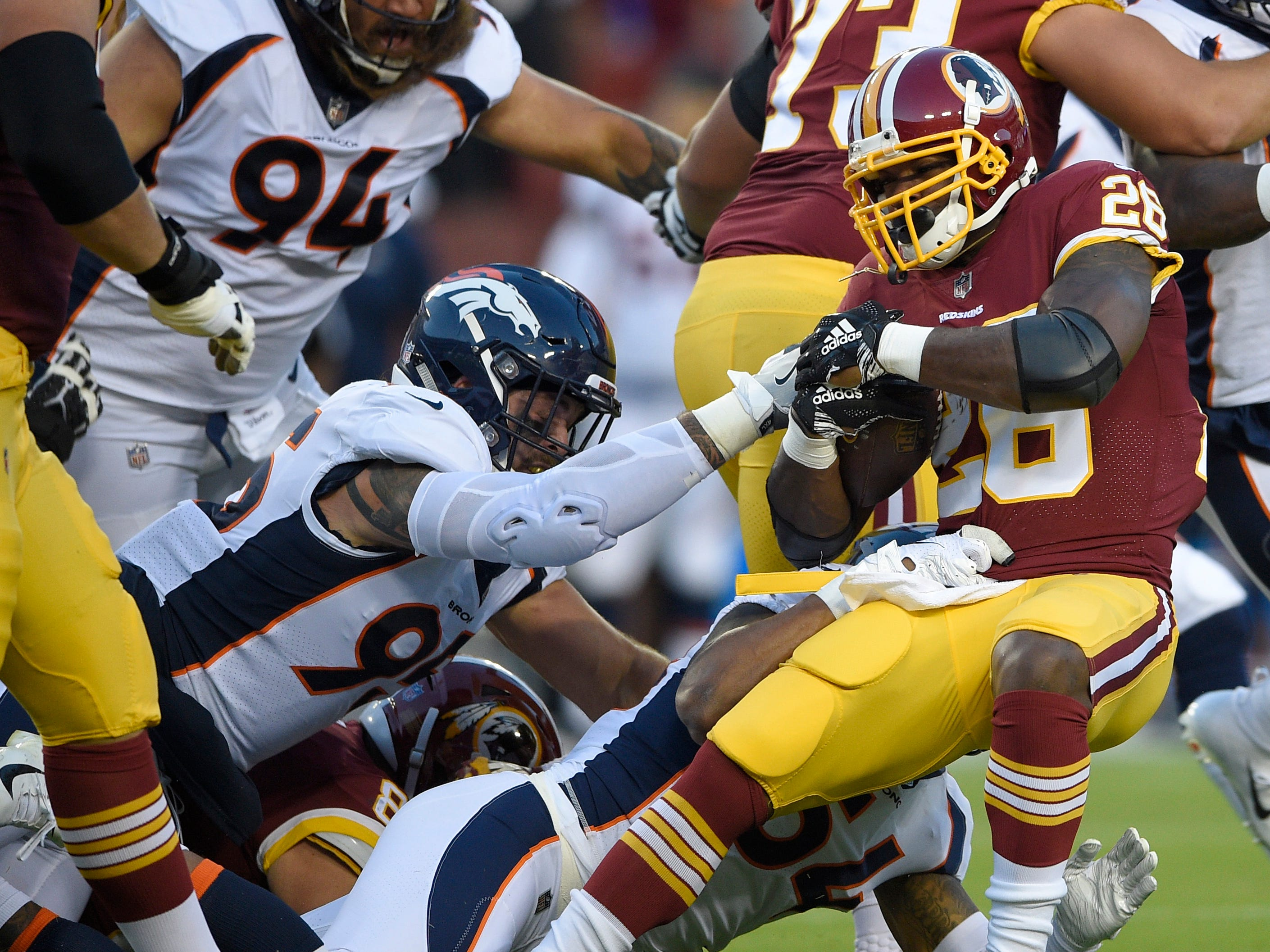 Washington Redskins running back Adrian Peterson (26) is tackled by Denver Broncos linebacker Brandon Marshall, back bottom, defensive end Derek Wolfe, left, during the first half of a preseason NFL football game, Friday, Aug. 24, 2018, in Landover, Md.