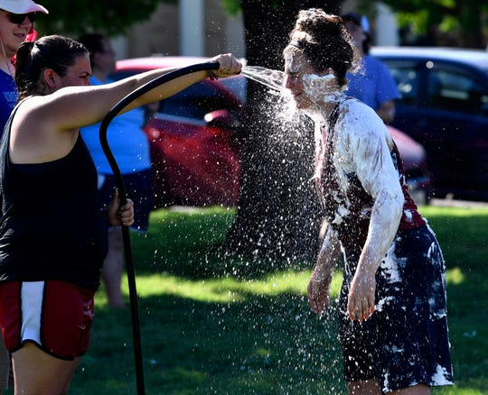 Monica Flores rinses the shaving cream from Shawna Faucett's face during Saturday's Slime Olympics. Part of Welcome Week, the annual event features teams of incoming McMurry University freshmen competing in a variety of slippery events.