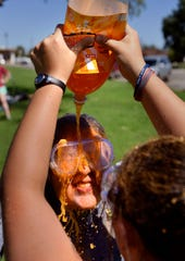 Monica Flores pours orange soda over Haley Shepard Saturday. The two women are McMurry University student orientation co-directors and started off the Slime Olympics with their own duel.