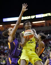 Seattle Storm's Natasha Howard (middle) cuts between Phoenix Mercury's Angel Robinson (left) and DeWanna Bonner.