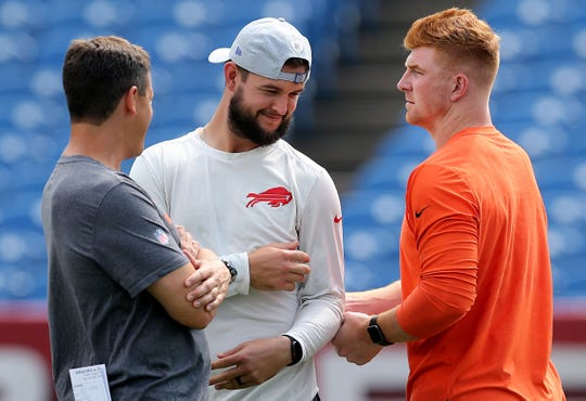 Cincinnati Bengals quarterback Andy Dalton (14), right, jokes with former Bengal now Buffalo Bills  quarterback AJ McCarron (10), center, before the Week 3 NFL preseason game between the Cincinnati Bengals and the Buffalo Bills, Sunday, Aug. 26, 2018, at New Era Stadium in Orchard Park, New York.