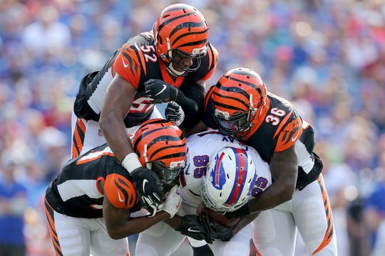 Cincinnati Bengals defensive back Darqueze Dennard (21), Cincinnati Bengals linebacker Preston Brown (52) and Cincinnati Bengals defensive back Shawn Williams (36) gang tackle Buffalo Bills tight end Charles Clay (85) in the first quarter during the Week 3 NFL preseason game between the Cincinnati Bengals and the Buffalo Bills, Sunday, Aug. 26, 2018, at New Era Stadium in Orchard Park, New York.