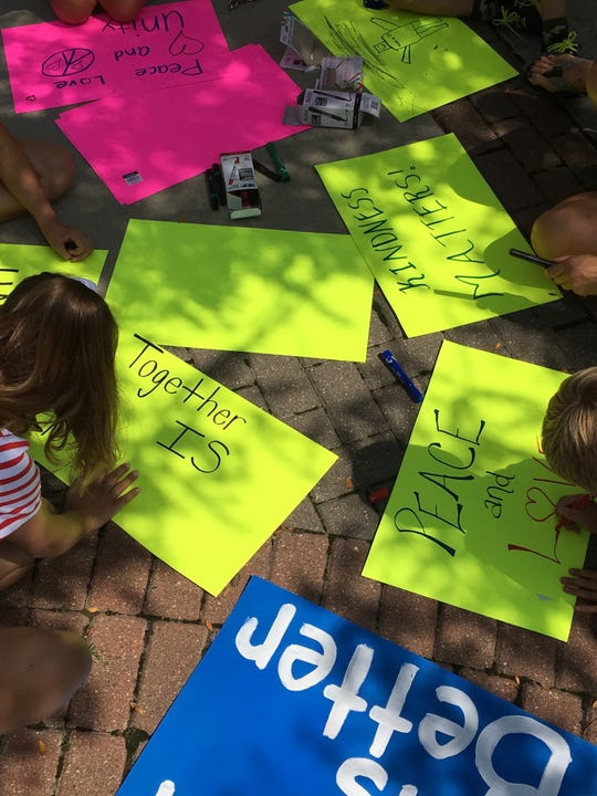 Peace Love and Unity rally attendees created posters with messages of support for the Latino community.