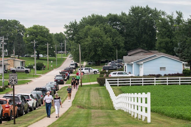 A line of people walk several blocks to attend Mollie Tibbetts' funeral at BGM High School after the parking lot outside the school had been filled on Sunday, Aug. 26, 2018, in Brooklyn.