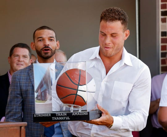 Blake Griffin tries to put a presentation basketball back on its stand inside a plastic case after it was presented to him by the men's and women's basketball team as the new Griffin Family Performance Center at the University of Oklahoma is dedicated on Saturday, Aug. 25, 2018 in Norman, Okla. Behind is senior associate athletic director Zac Selmon.