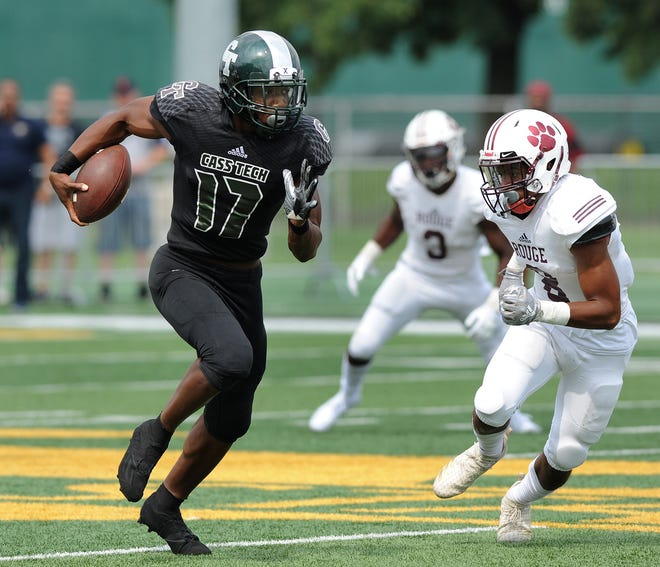 Detroit Cass Tech quarterback Jalen Graham scrambles for yardage as he is chased by River Rouge cornerback David Carter during the first quarter Saturday. Cass Tech won, 40-7.
