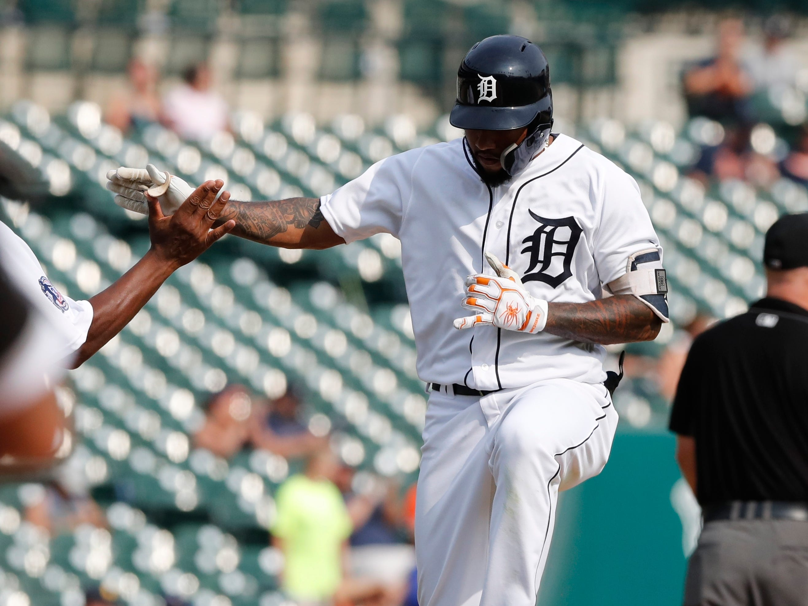 Detroit Tigers' Ronny Rodriguez jumps as he is greeted by third base coach Dave Clark after a solo home run during the ninth inning.