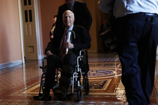 U.S. Sen. John McCain (R-AZ) passes by on a wheelchair in a hallway at the Capitol December 1, 2017 in Washington, DC. Senate GOPs indicate that they have enough votes to pass the tax reform bill.