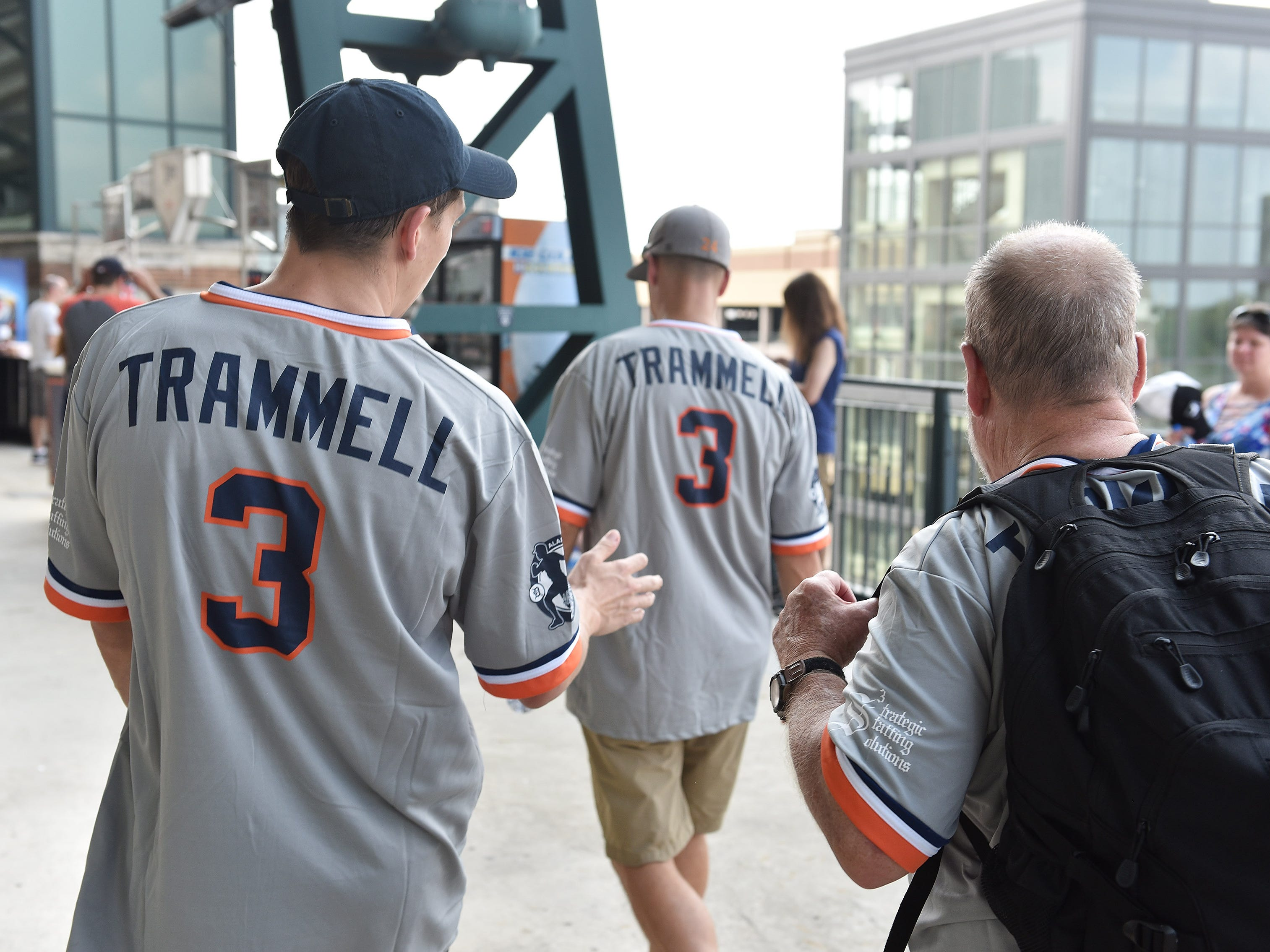Gatlin Griffin of Tampa, Fla, left, talks with his grandfather, Bruce Griffin of Flagstaff, Ariz., right, following his father, Thomas Griffin of Phoenix while walking at the ballpark.  Bruce Griffin was born in Flint and became a Tigers fan before he moved out of state. The three generations wanted to be at the game for the retiring of Alan Trammell's number.