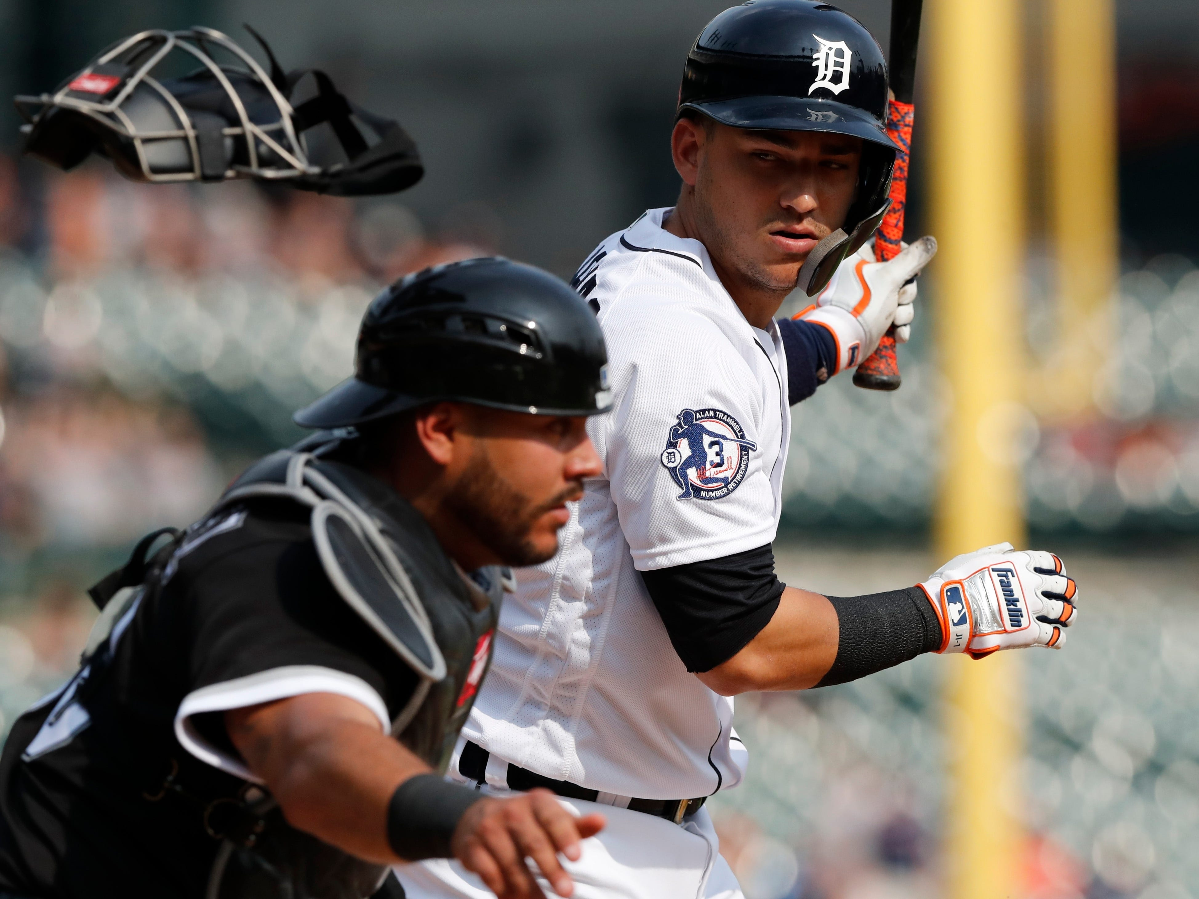 Detroit Tigers' Jose Iglesias looks back as Chicago White Sox catcher Omar Narvaez chases the ball after Iglesias struck out to end the baseball game.