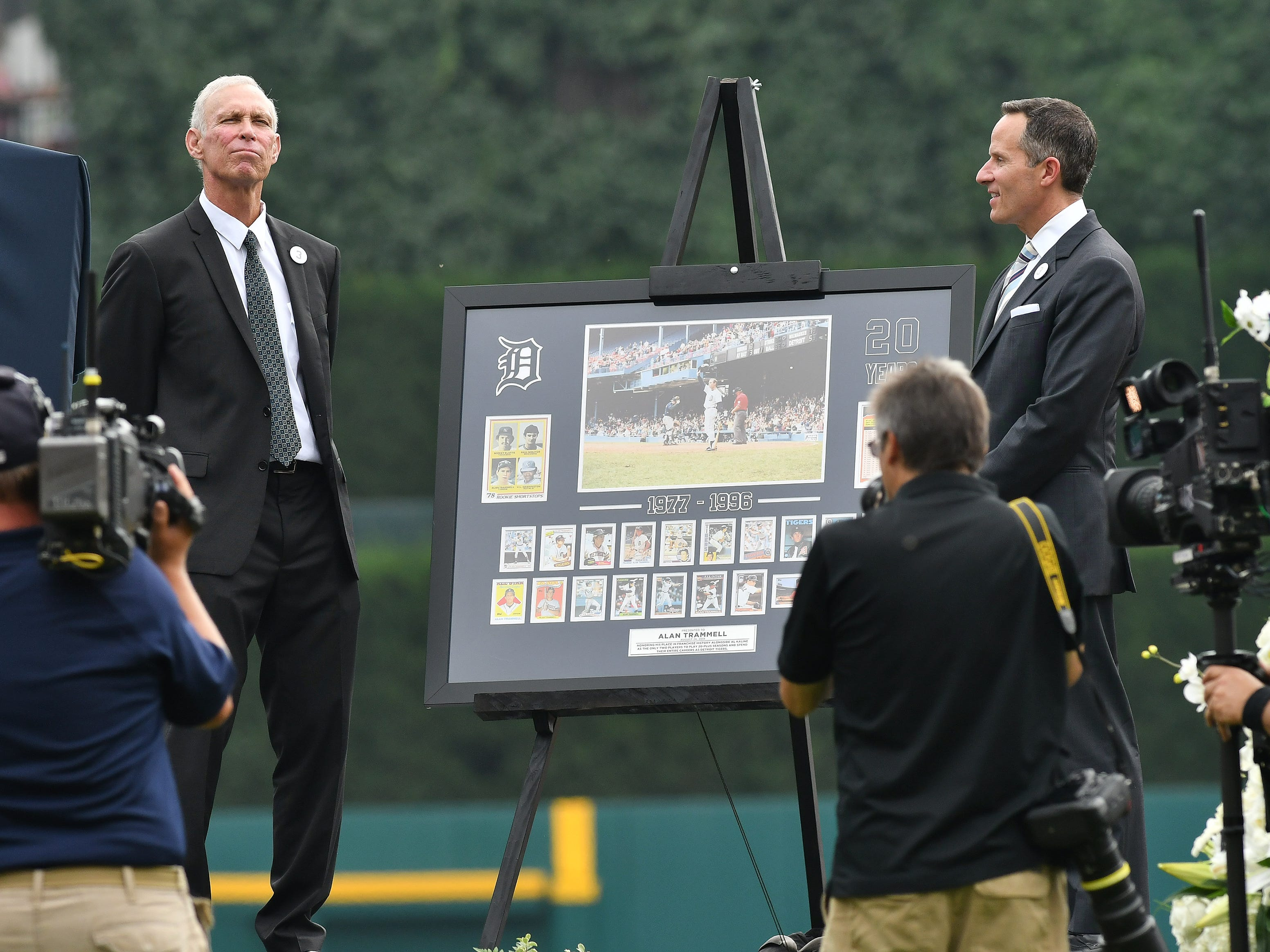 President and CEO of Ilitch Holdings, Inc. Chris Ilitch, right, presents Alan Trammell with a framed collection of his baseball cards during a special pregame ceremony to retire Trammell's No. 3.