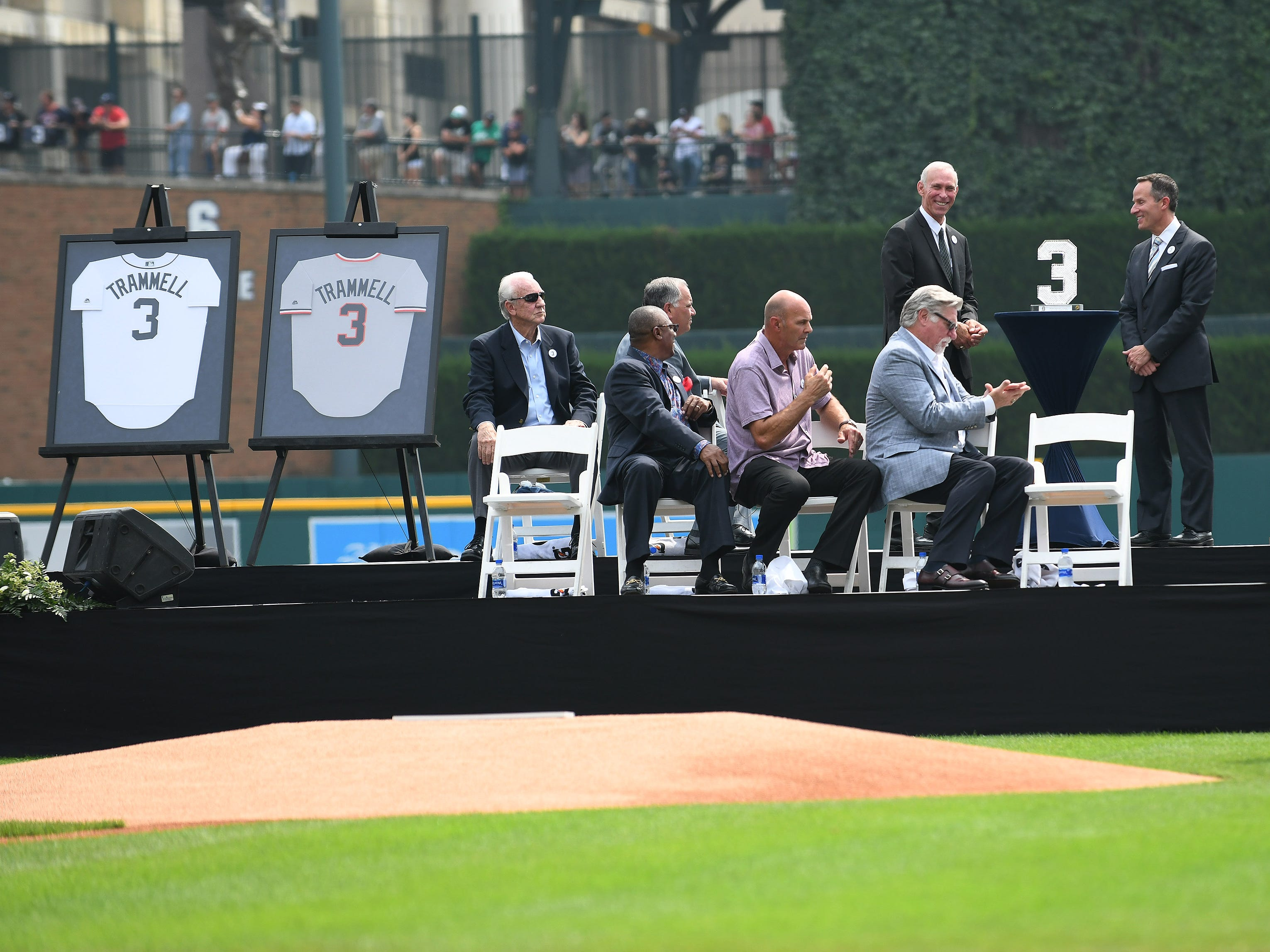 President and CEO of Ilitch Holdings, Inc. Chris Ilitch, right, presents Alan Trammell with a Waterford crystal of his number 3 during the ceremony.