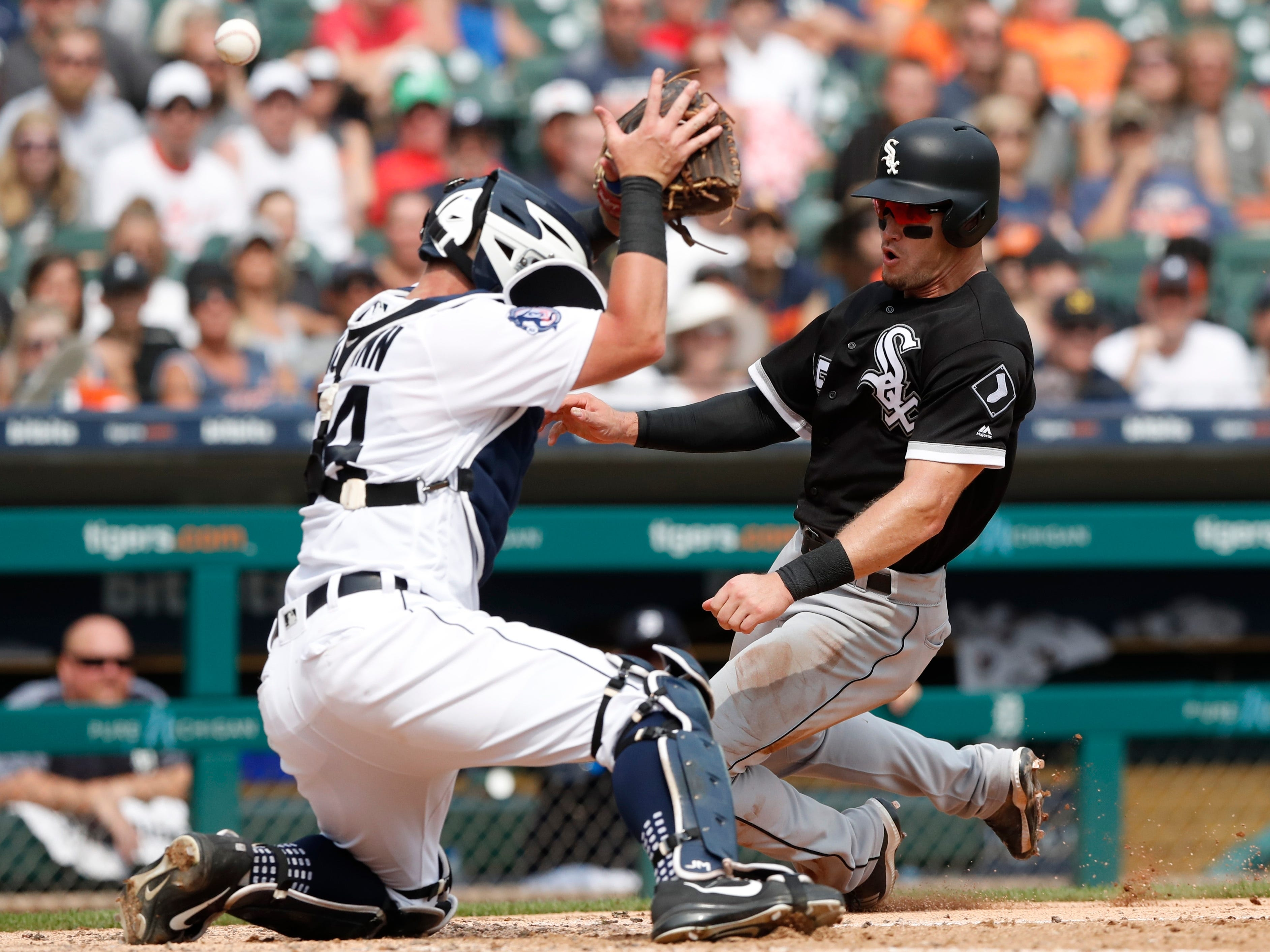 Detroit Tigers catcher James McCann reaches but misses a high throw as Chicago White Sox's Adam Engel safely slides to score seventh inning.