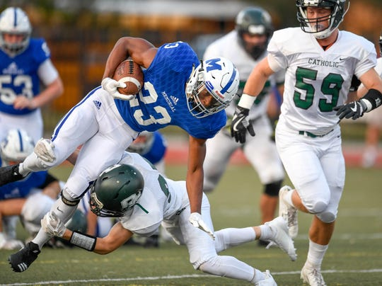 Owensboro Catholic's Hagan Edge (25) takes the legs from under Memorial's Darius Johnson (23) as the Evansville Memorial Tigers play the Owensboro Catholic Aces at the Border Bowl played at Enlow Field in Evansville Saturday, August 25, 2018.