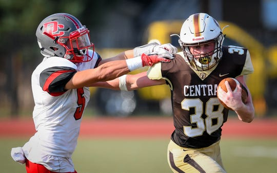 Central's Brennan Schutte (38) pushes off Daviess County's Blake Baker (5) during a long run as the Daviess County Panthers play the Evansville Central Bears at the Border Bowl played at Enlow Field in Evansville Saturday, August 25, 2018.
