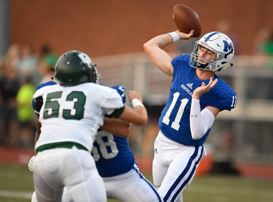 Memorial's Michael Lindauer (11) passes over defense from Owensboro Catholic's Tim Settles (53) as the Evansville Memorial Tigers play the Owensboro Catholic Aces at the Border Bowl played at Enlow Field in Evansville Saturday, August 25, 2018.