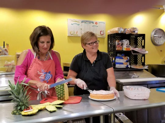 Nancy McCarnan, left, and Robin Cook  work in the open kitchen at the Sidewalk Cafe.
