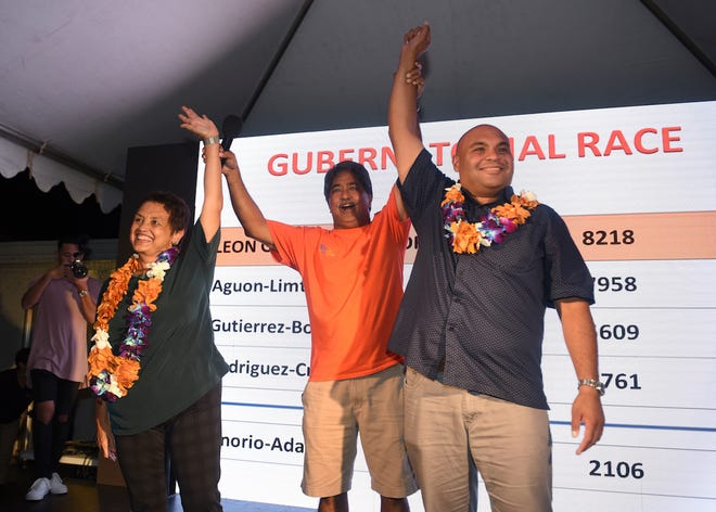 Former Sen. Francis Santos, center, raises the arms of gubernatorial candidate Lou Leon Guerrero, left, and her running mate, Joshua Tenorio, after the team was announced as winners early Sunday morning, Aug. 26, 2018, in Saturday's Democratic primary.