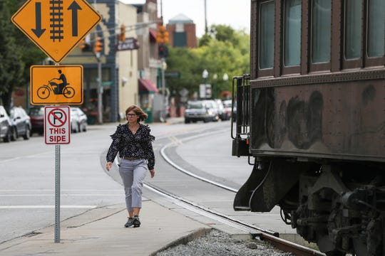 A pedestrian passes by a passenger train car parked on the Nickel Plate tracks near Logan Street and 8th Street in downtown Noblesville, Wednesday, Aug. 22, 2018. The 70-foot-long passenger rail car from 1929 is on loan to the Nickel Plate Express, but the train operator doesn't have anywhere to put it yet. It will be parked on the square until at least December and and then taken to a storage yard in Arcadia.