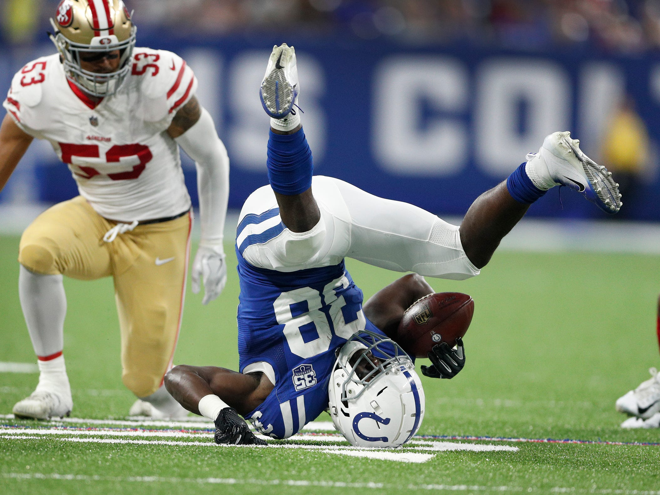 Indianapolis Colts running back Christine Michael (38) is knocked backwards by San Francisco 49ers outside linebacker Mark Nzeocha (53) in the second half of their preseason football game at Lucas Oil Stadium Saturday, August 25, 2018. The Colts defeated the 49ers 23-17.