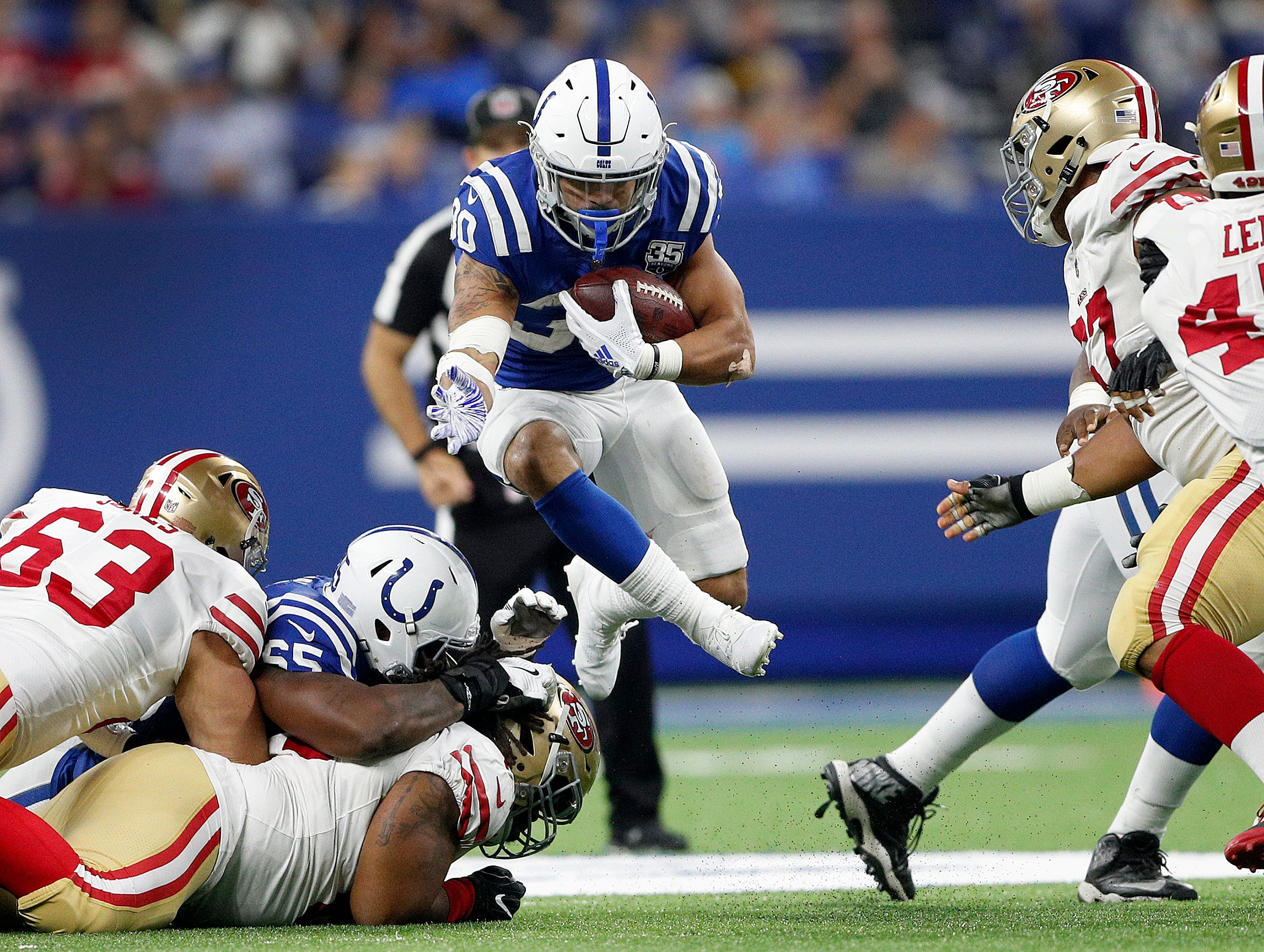 Indianapolis Colts running back Jordan Wilkins (30) jumps over linemen in the second half of their preseason football game at Lucas Oil Stadium Saturday, August 25, 2018. The Colts defeated the 49ers 23-17.