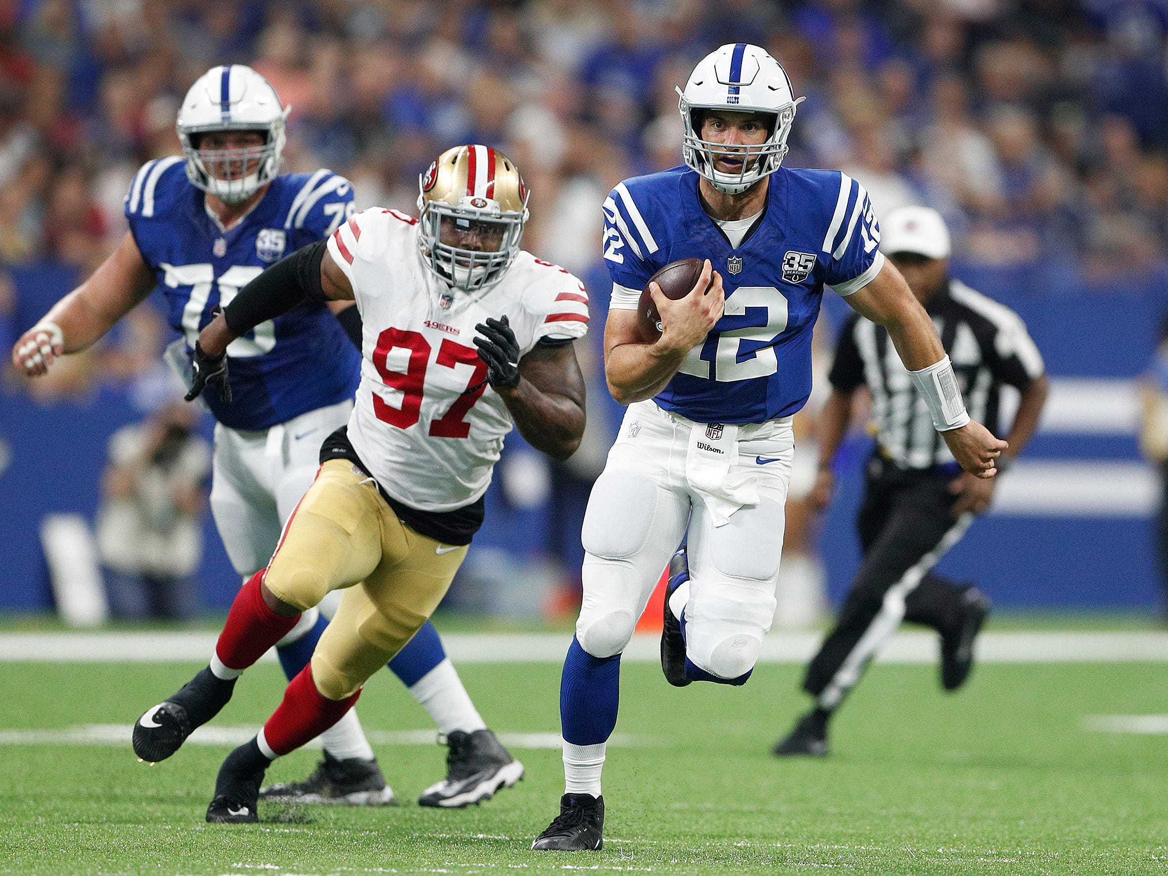 Indianapolis Colts quarterback Andrew Luck (12) runs for a first down in the first half of their preseason football game at Lucas Oil Stadium Saturday, August 25, 2018.