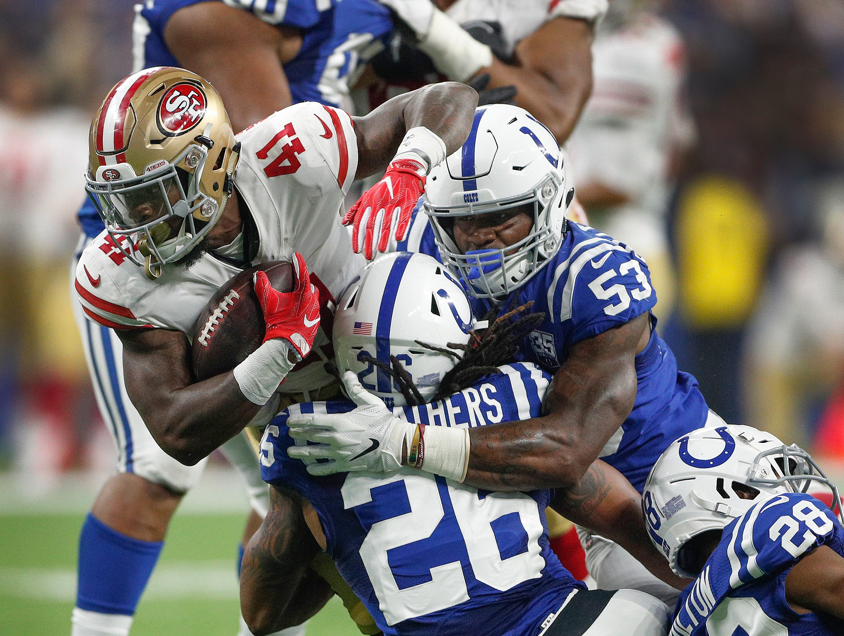 Indianapolis Colts linebacker Darius Leonard (53) and Clayton Geathers (26) team up to tackleSan Francisco 49ers running back Jeff Wilson (41) in the first half of their preseason football game at Lucas Oil Stadium Saturday, August 25, 2018.