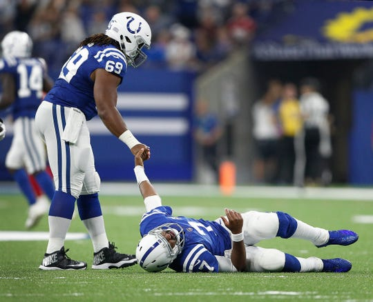 Indianapolis Colts offensive guard Deyshawn Bond (69) attempts to help up Indianapolis Colts quarterback Jacoby Brissett (7) after he was hit in the second half of their preseason football game at Lucas Oil Stadium Saturday, August 25, 2018. The Colts defeated the 49ers 23-17.