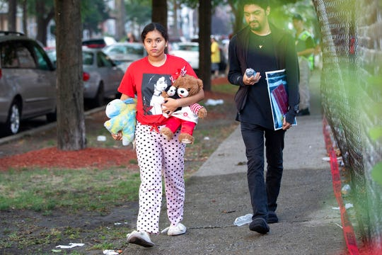 People carry things away from the scene of a fire that killed several people including multiple children Sunday, Aug. 26, 2018, in Chicago. The cause of the blaze hasn't been determined.