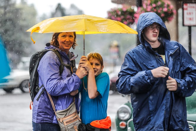 Right to left, Karen, Rich, and Nick Ostendorf braved the rain to see hundreds of cars during the 2018 Artomobilia Car Show in Carmel Ind. on Sat. Aug 25, 2018.