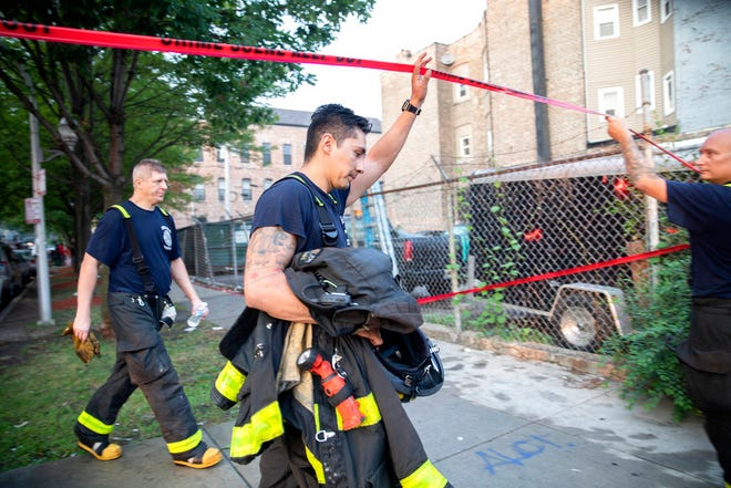 Chicago firefighters walk under tape at the scene of a fire that killed several people including multiple children Sunday, Aug. 26, 2018, in Chicago. The cause of the blaze hasn't been determined.