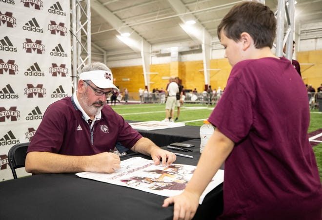 Head coach Joe Moorhead signs an autograph for a young Bulldogs fan at Mississippi State's 2018 Fan Day.