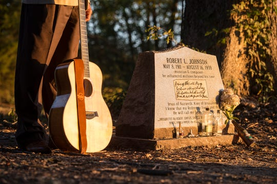 Itta Bena sits in the middle of three grave markers dedicated to blues musician Robert Johnson.