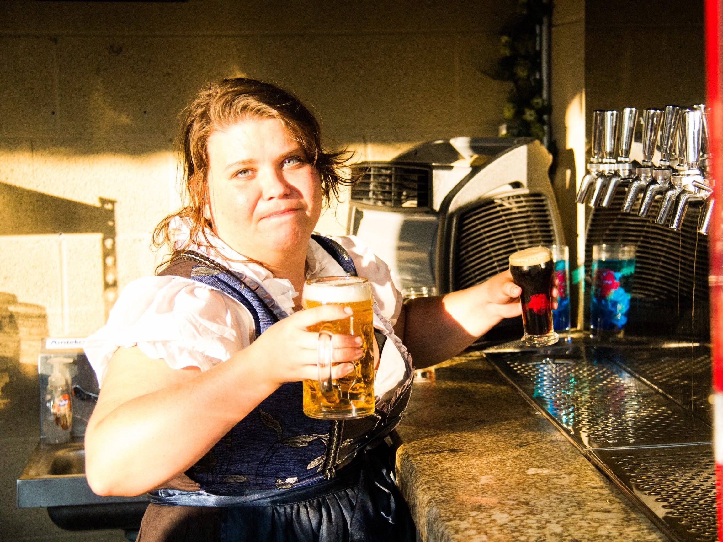 A bartender at Schulz Brau pours beer for customers attending the free Sunset on Central festival Saturday.