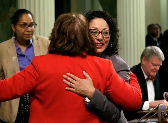 FILE - In this May 25, 2018, file photo, Assemblywoman Cristina Garcia, D-Bell Gardens, right, is embraced by Assemblywoman Eloise Gomez Reyes, D-Grand Terrace, on her first day back at the Assembly in Sacramento, Calif. Until the new process is in place, people who brought complaints in the wake of #MeToo are still going through an old process that has prompted concerns. Earlier this summer, for example, California legislative leaders reopened an investigation into Garcia after her accuser claimed an initial review that failed to substantiate a groping complaint was unfair and incomplete. (AP Photo/Rich Pedroncelli, File)