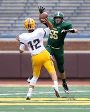 Howell's DJ Hamilton gets a hand in the face of Dearborn Fordson quarterback Hussein Ajami during the season opener at Michigan Stadium on Saturday, Aug. 25, 2018.