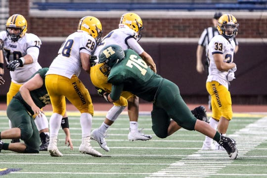 Howell's Grant Porter hits Dearborn Fordson quarterback Hussein Ajami in the Highlanders' 48-28 loss at Michigan Stadium on Saturday, Aug. 25, 2018.