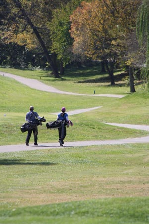 Golfers carry their bags to their next shot at Cherokee Park Golf Course.