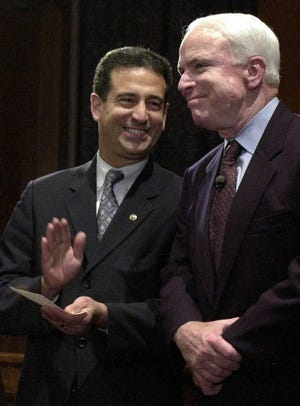 Sen. Russ Feingold (left), D-Wisconsin,  and Sen. John McCain, R-Arizona, smile during a rally on Capitol Hill on March 20, 2002, following a vote on campaign finance reform.