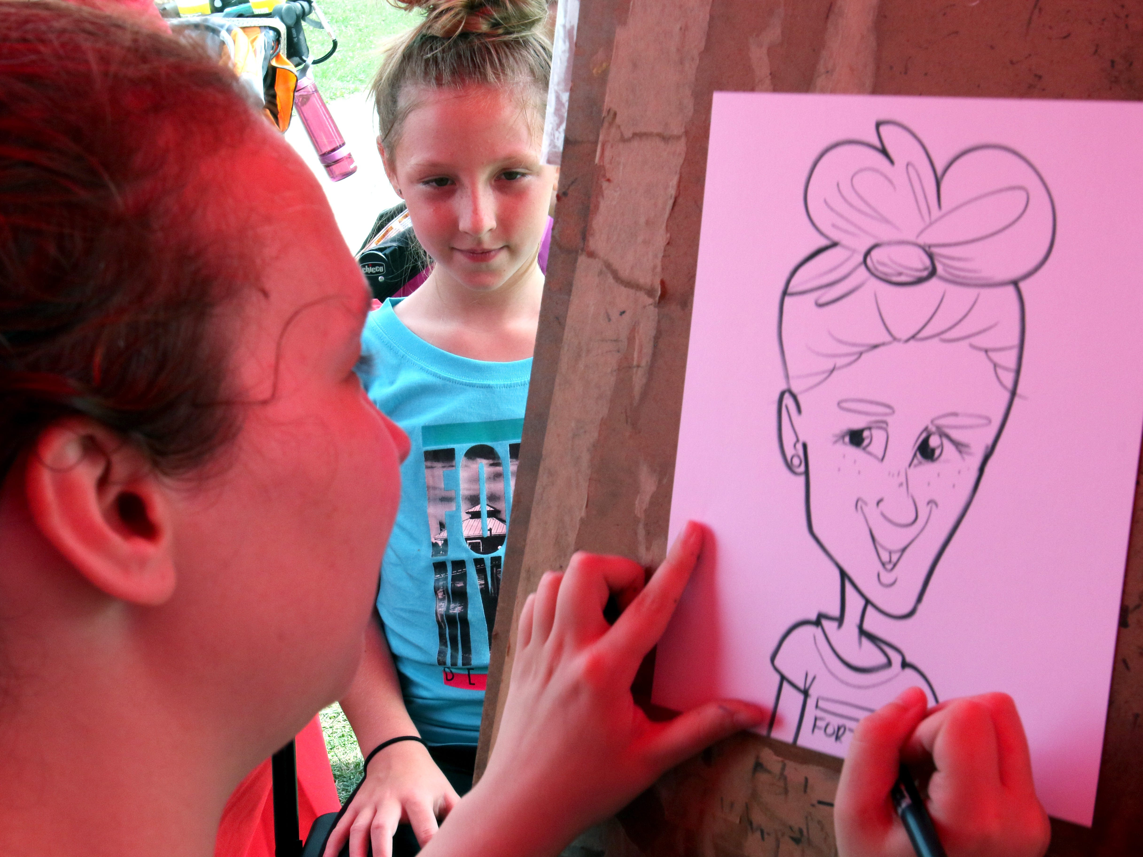 Rebecca McConnell creates a caricature of of Lily Unger, 10, at the State Farm Insurance booth during the Muskego Community Festival at Muskego Veterans Memorial Park on Aug. 25.