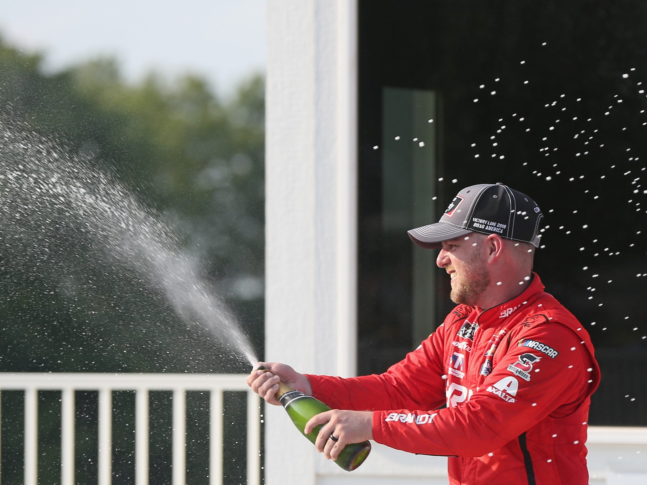 Justin Allgaier celebrates in victory lane after winning the NASCAR Xfinity Series Johnsonville 180 at Road America on Saturday by spraying a little champagne.